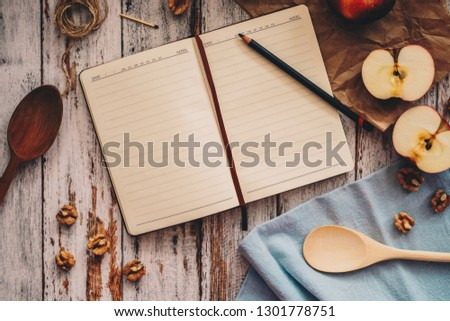Cooking a recipe book with apple walnuts and spoon on wooden and