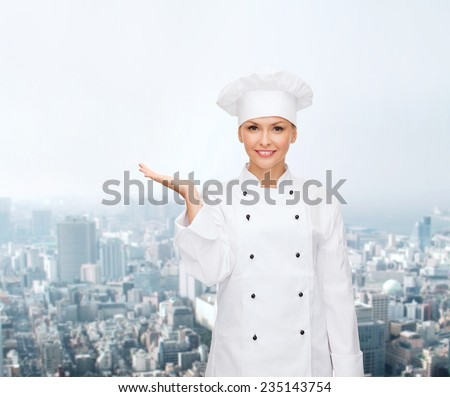 cooking, advertisement and people concept - smiling female chef, cook or baker holding something on palm of hand over city background