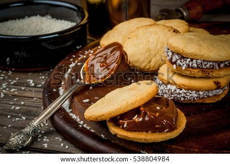 Shutterstock Cooking alfajores - a traditional dessert from Latin America or Mexico. Shortbread cookies with dulce de leche and coconut