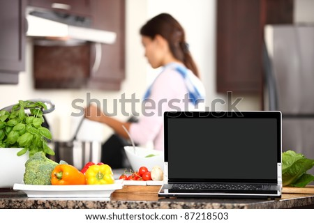 cooking and computer laptop concept. Blank pc monitor screen in focus with cooking woman in kitchen.