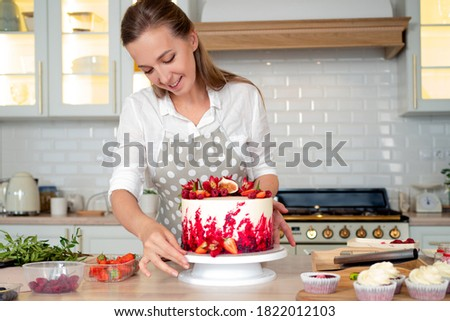 cooking and decoration of cake with cream. Young woman pastry chef in the kitchen decorating red velvet cake. Happy woman in apron in kitchen makes beautiful birthday cake, cooking and pastry skills