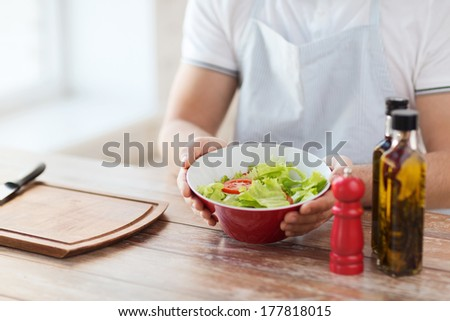 cooking and home concept - close of male hand holding a bowl with salad