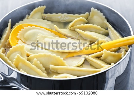 Cooking and stirring pot of ravioli pasta in boiling water