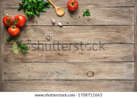 Cooking background, home cooking concept. Ripe tomatoes, spoon, herbs and spices on wooden background, top view, copy space.