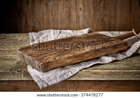 Cooking background with old wooden cutting board and linen kitchen towel #374478277