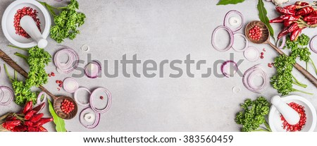 Cooking background with spices mortar , wooden spoon and various fresh seasoning on gray stone background, top view, banner.