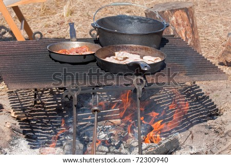 Cooking bacon in an iron skillet on an open campfire