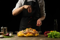 Cooking chef duck sprinkle with grains of pomegranate frozen, horizontal photo, black background