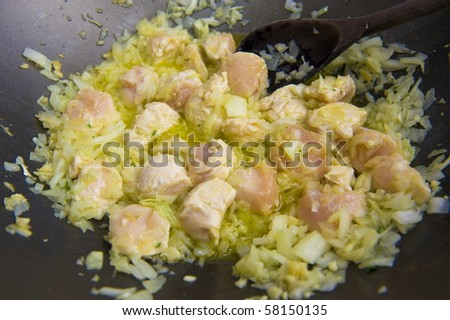 Cooking chicken with onion and garlic .