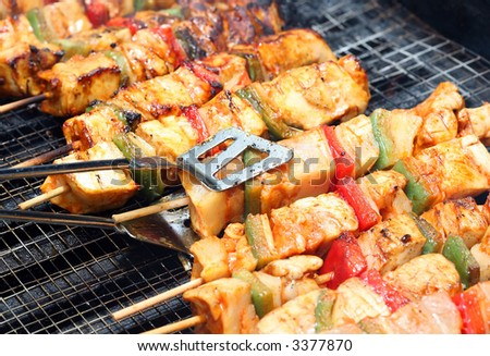 cooking chicken with pepper on outdoor barbecue