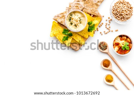 Cooking chickpeas. Bowl with hummus among pieces of crispbread and spices on white background top view copy space #1013672692