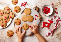 Cooking Christmas gingerbread.  Child's hand decorating red nosed reindeer cookies with chocolate buttons and melted chocolate. Festive homemade decorated sweets