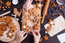 Cooking Christmas gingerbread. Friends decorating freshly baked cookies with icing and confectionery mastic, view from above. Festive food, family culinary, Christmas and New Year traditions concept