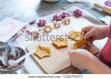 cooking class, culinary. food and people concept/ molding of pelmeni or meat dumplings, child hands in process