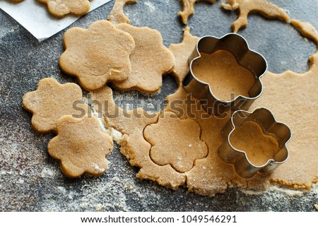 Cooking cookies with  cookie cutters on a dark table