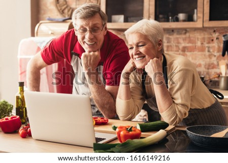 Cooking courses online. Senior couple watching video recipes on laptop at kitchen