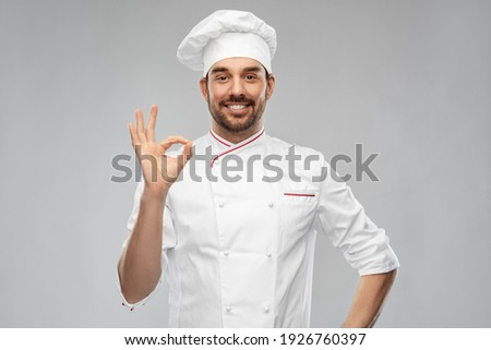 cooking, culinary and people concept - happy smiling male chef in toque showing ok hand sign over grey background Stock photo ©