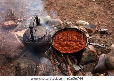 cooking dinner on campfire in...