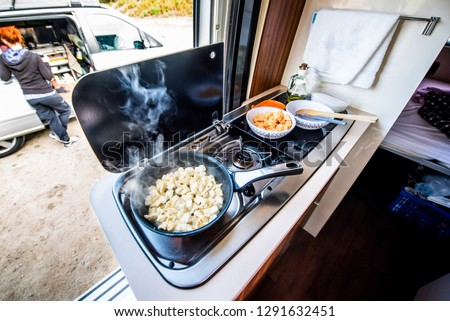 Cooking dinner or lunch in campervan, motorhome or RV. Preparing chicken  in a pan in camper van when traveling with RV, motor home caravan or motorvan. Vanlife or van life lifestyle on the road.