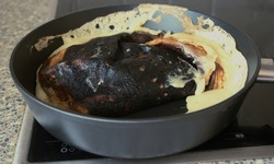 Cooking fail. Burned omelet in pan close-up. Amateur culinary