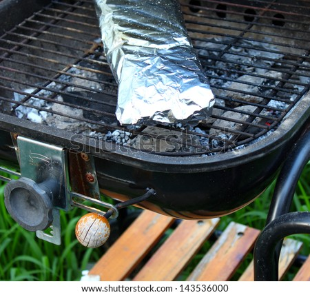 Cooking fish in foil on barbecue. Background.