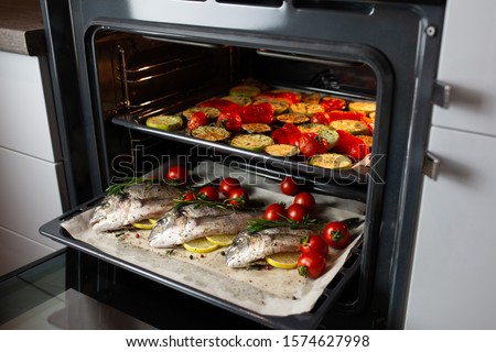 Cooking fish in the oven.Cooking dorado with cherry tomatoes and herbs on parchment in the oven.The supper is ready.We bake sea bass on a grill.Girl cooks fish and takes it out of the stove.World food