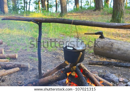 Cooking fish soup on the fire in the forest camp