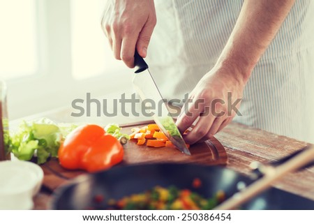 cooking, food and home concept - close up of male hand cutting pepper on cutting board at home