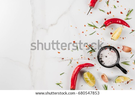 Shutterstock Cooking food background, White marble table with spices - hot red pepper, seasonings, garlic, salt, greens, tarragon, parsley, herbs, lime lemon, top view copy space