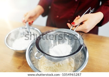cooking food, baking and people concept - chef with strainer sieving flour into bowl and making batter or dough - Shutterstock ID 1054965287