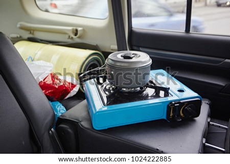 Cooking food in a saucepan on a portable gas stove inside the car. Mobile kitchen in the city. #1024222885