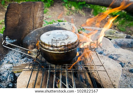 Cooking food with old tourist pot at outdoor fire place. Summer trekking activity