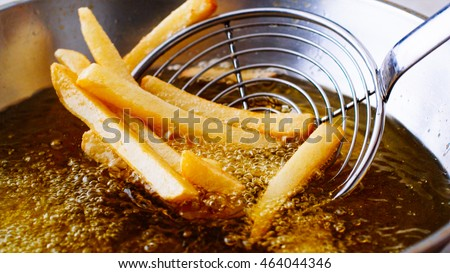 Cooking french fries. Close up of Frying french fries in the fryer in hot oil ストックフォト ©