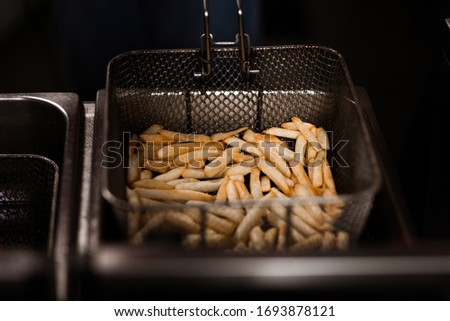 cooking french fries in the kitchen, the chef cooks french fries, a deep fryer with french fries, fry in oil