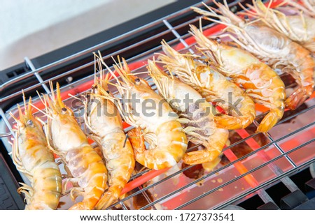 Cooking grilled shrimp with an electric grill by grilled on Steel grating The bottom has a hot conductive wire which was so hot that it was red.