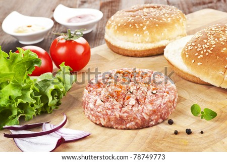 Cooking hamburger. Minced raw meet with fresh vegetable and bun on wooden cutting board.