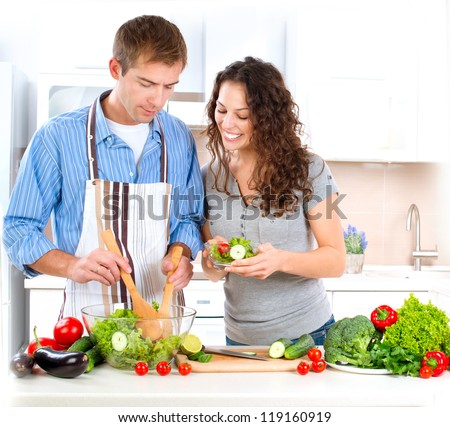 Cooking.Happy Couple Cooking Together - Man and Woman in their Kitchen at home Preparing Vegetable Salad.Diet.Dieting. Healthy Food Tasting