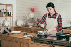 Cooking happy woman wear pinafore in wooden kitchen with pot stir melting chocolate to make sweet dessert for valentine day. young beautiful girlfriend handmade cocoa using spoon cooking on stove.