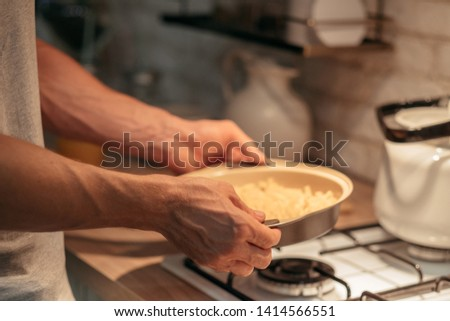 Cooking hobby and leisure. Traditional culinary recipe. Closeup of man hands holding frying pan with ready dinner meal. #1414566551