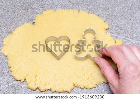 Cooking homemade cookies concept. A female hand cuts out a cookie blank in the shape of one gingerbread man and a heart from the dough on a gray background. Searching for love concept stock photo
