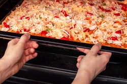 Cooking homemade pizza in the oven. A young woman puts uncooked pizza in the oven on a baking pan. Appetizing pizza with delicious ingredients cooked in oven.