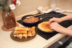 Cooking homemade Russian pancakes Bliny with meat on Shrovetide - Maslenitsa. Woman cooks pancakes in her kitchen.