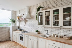 Cooking hood over gas stove appliance, built in oven equipment, sink and water tap, kitchenware supplies on shelves, green plants on cupboard furniture. Side view of white kitchen facade in apartment