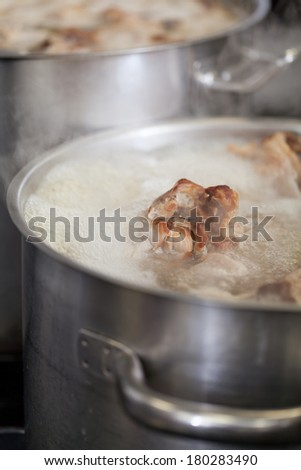 Cooking in a commercial kitchen with large stainless steel pots filled with stew and vegetables on a central gas hob