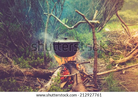 Cooking in field conditions, boiling pot at the campfire on picnic. Filtered image:cross processed vintage effect.