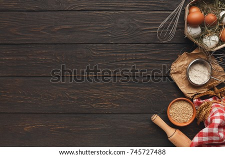 Cooking ingredients background. Border of flour and wheat grains in bowls, eggs and whisk on dark rustic wood with copy space. Dough preparing and pastry concept, top view #745727488