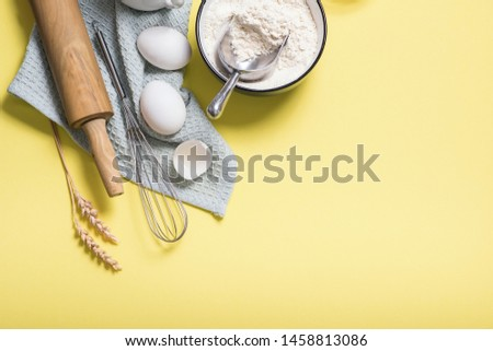 Cooking ingredients, flour, rolling pin and olive oil, top view, place for text yellow background, baking concept