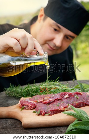 Cooking ingredients: marinated meat,oil,vinegar, herbs and vegetables