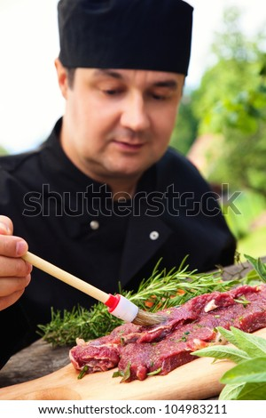 Cooking ingredients: marinated meat,oil,vinegar, herbs and vegetables. Chef is carving and marinating meat.