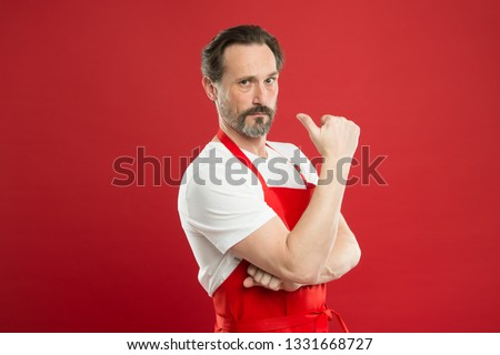 Cooking is passion. Cook with beard and mustache wear apron red background. Man mature cook posing cooking apron. Fine recipe. Ideas and tips. Chief cook and professional culinary. Cook food at home.